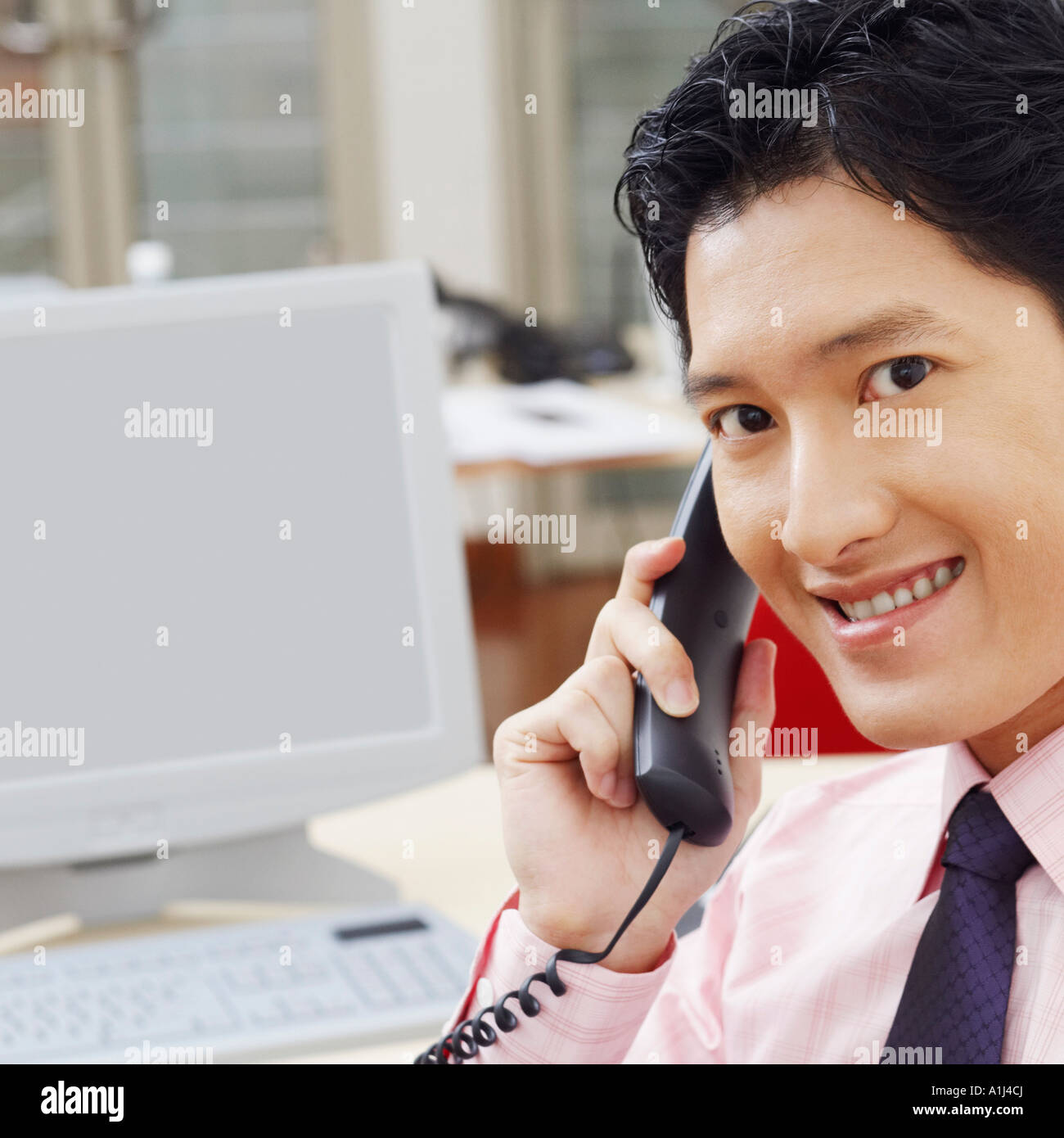 Portrait of a businessman talking on the telephone and smiling - Stock Image