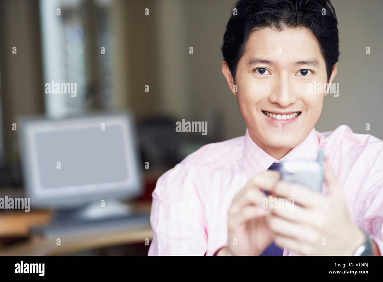 Portrait of a businessman operating a personal data assistant with a digitized pen and smiling - Stock Image
