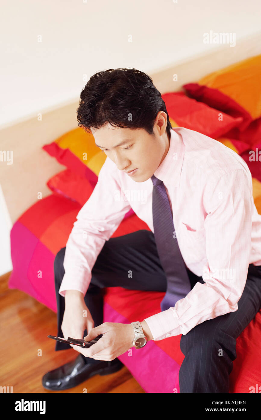 High angle view of a businessman sitting on the bed and operating a mobile phone - Stock Image