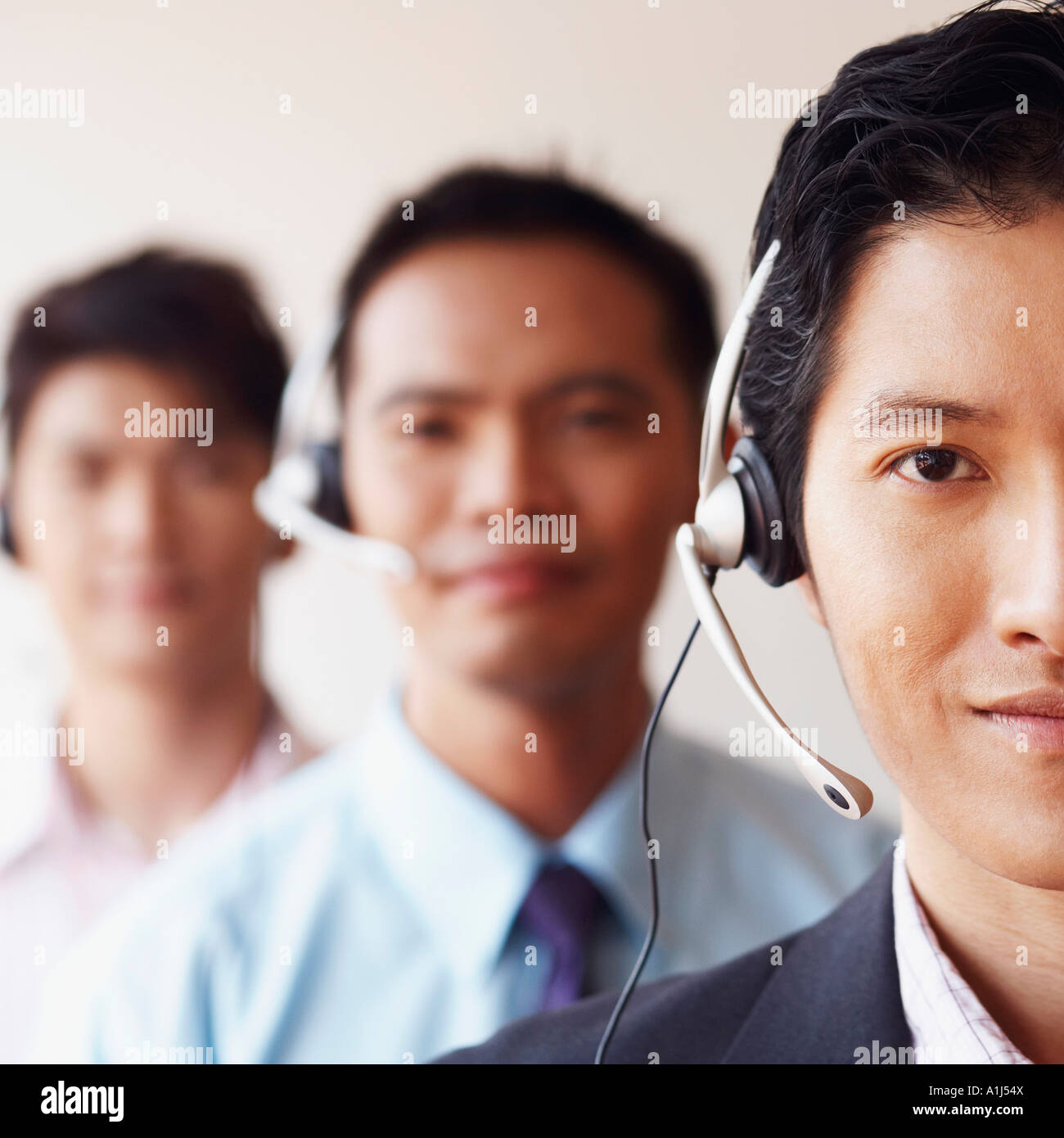 Portrait of three male customer service representatives - Stock Image
