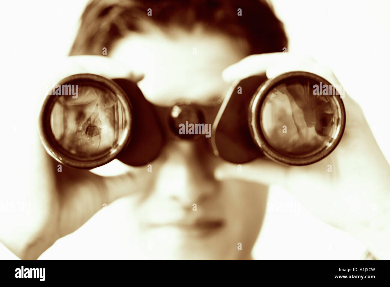 Close-up of a businessman looking through a pair of binoculars - Stock Image