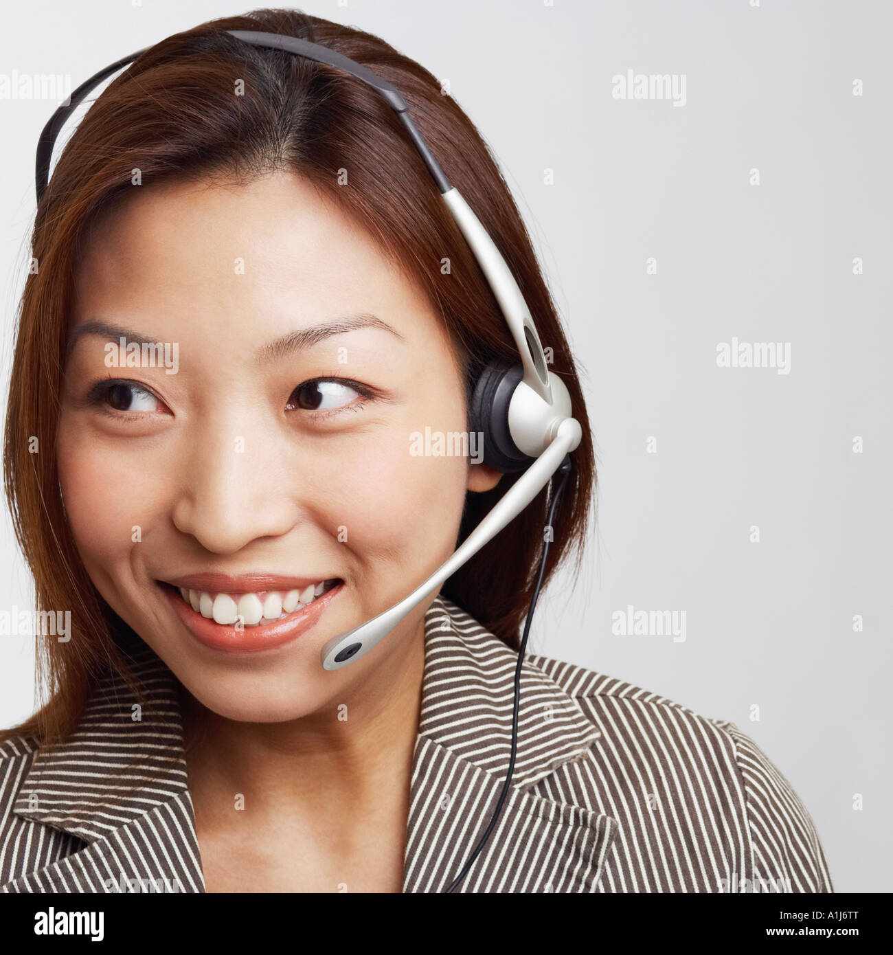 Close-up of a businesswoman wearing a headset and smiling Stock Photo