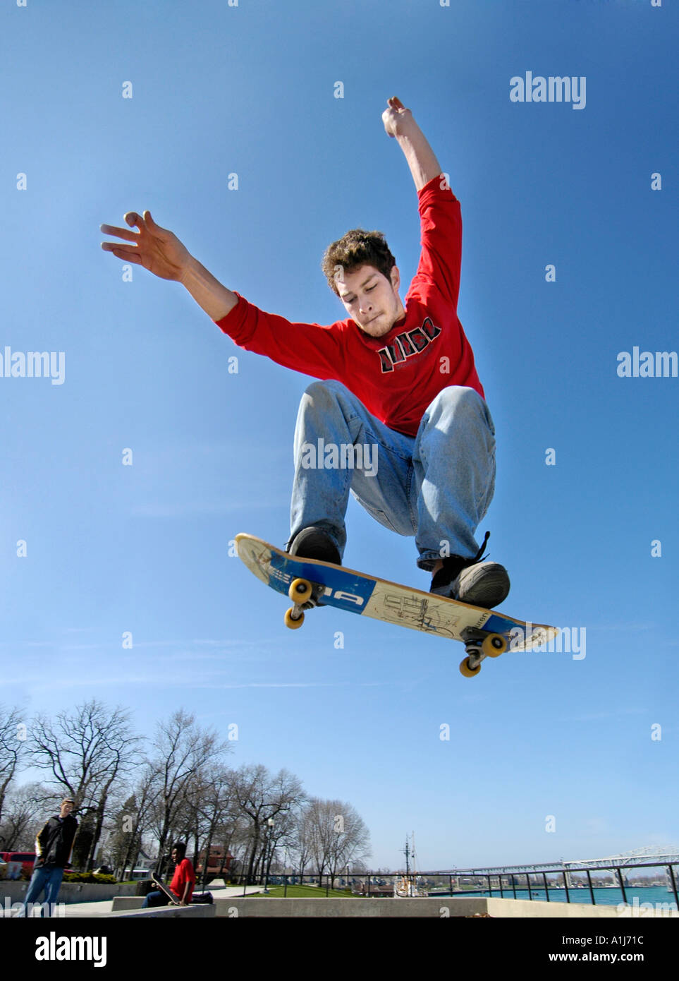 Male teen practices maneuvers on a skate board while jumping high into the air - Stock Image