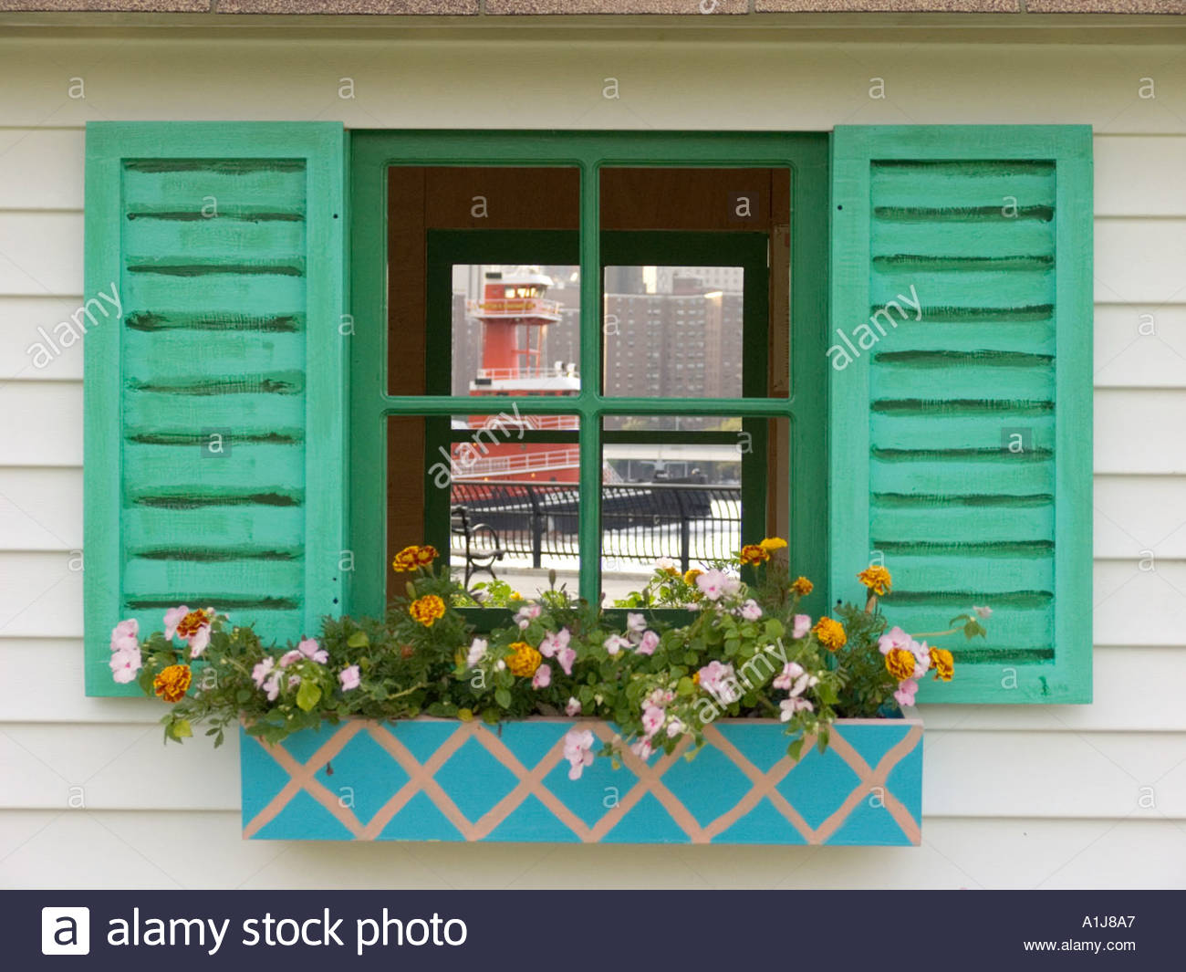 idyllic windows with flower box looking out to our world tugboat on the East River NYC Stock Photo