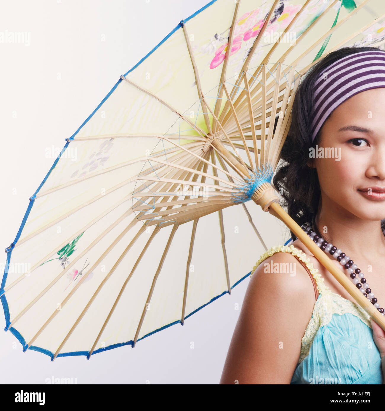 Portrait of a young woman holding a parasol and smiling - Stock Image