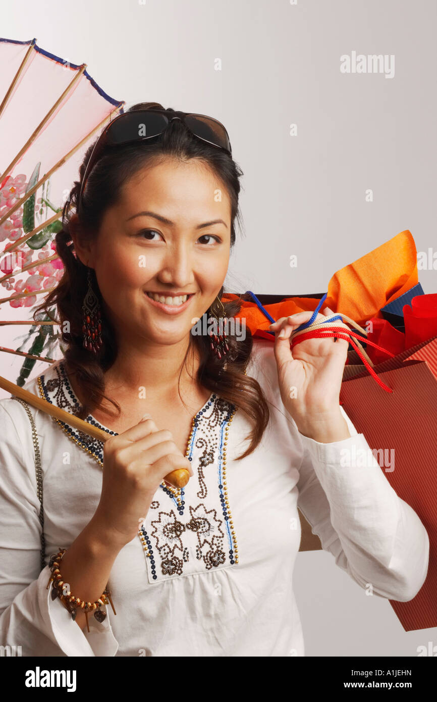 Portrait of a young woman holding shopping bags and smiling - Stock Image