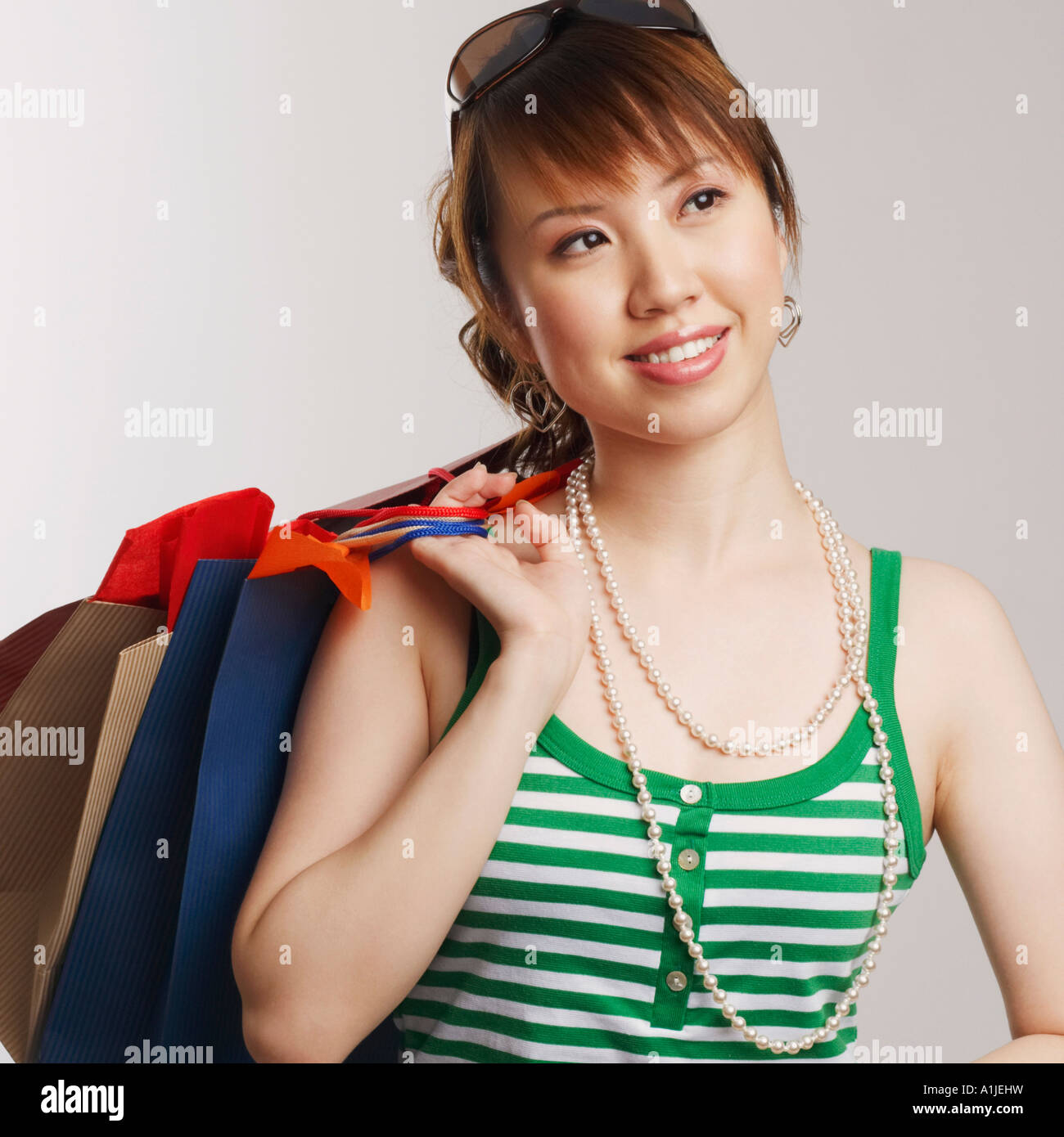 Close-up of a young woman carrying shopping bags and looking up - Stock Image