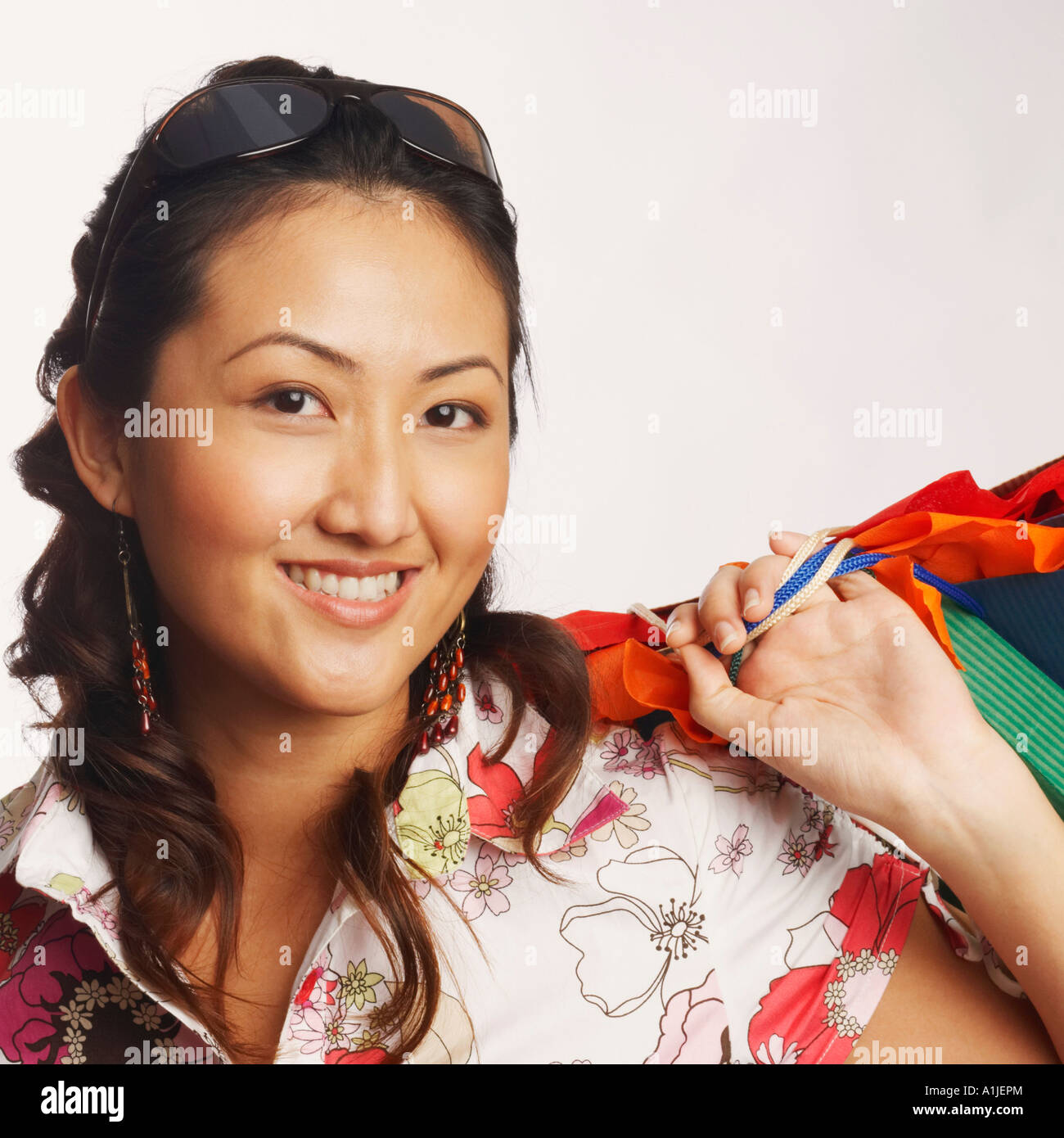 Portrait of a young woman carrying shopping bags and smiling - Stock Image