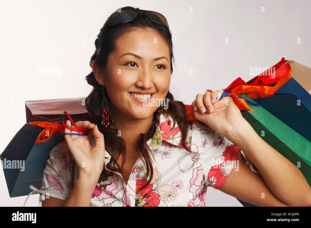 Close-up of a young woman carrying shopping bags and smiling - Stock Image