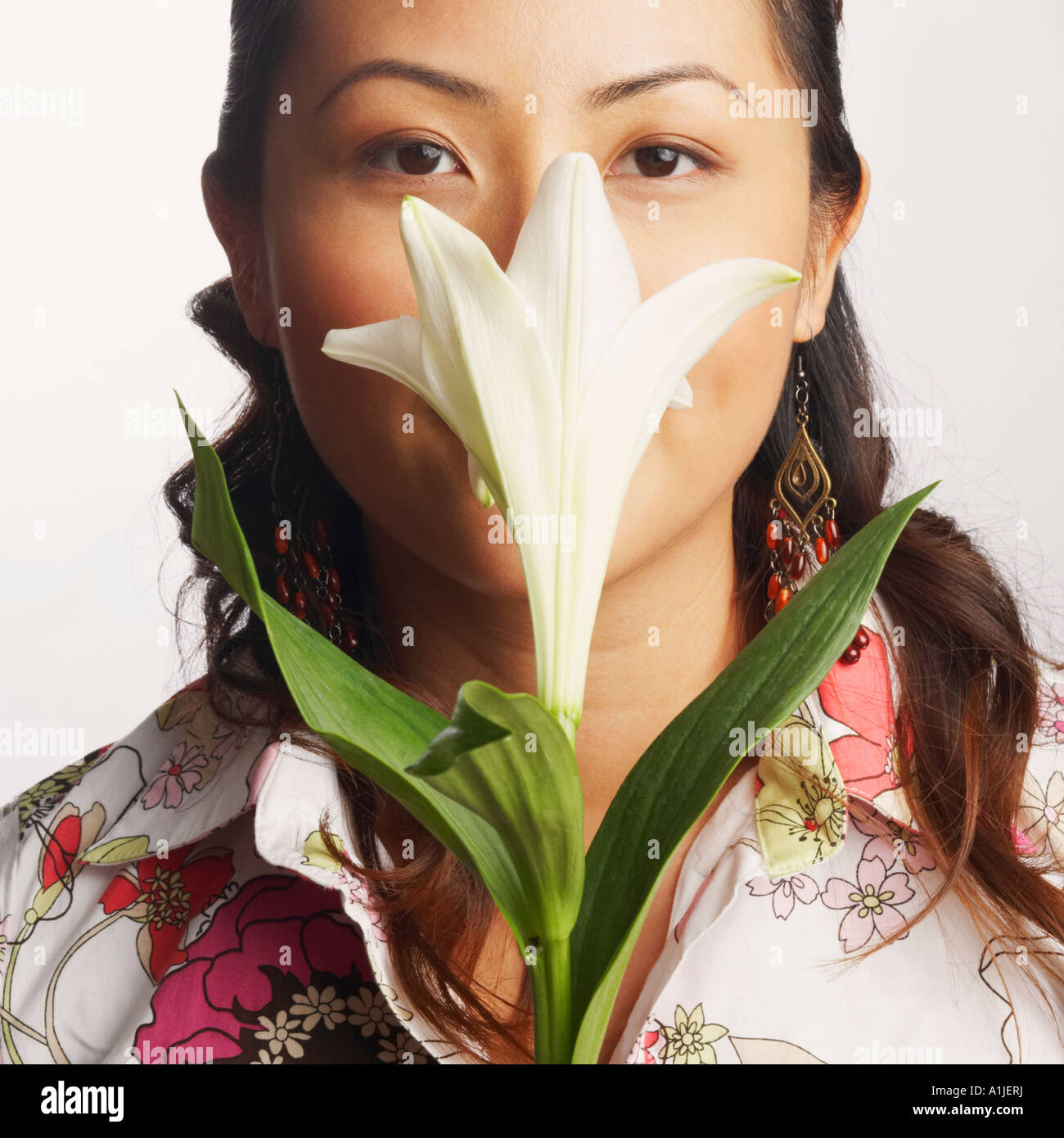 Close-up of a young woman smelling a flower - Stock Image
