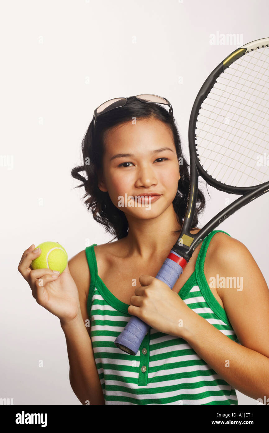 Portrait of a young woman holding a tennis racket and a tennis ball - Stock Image