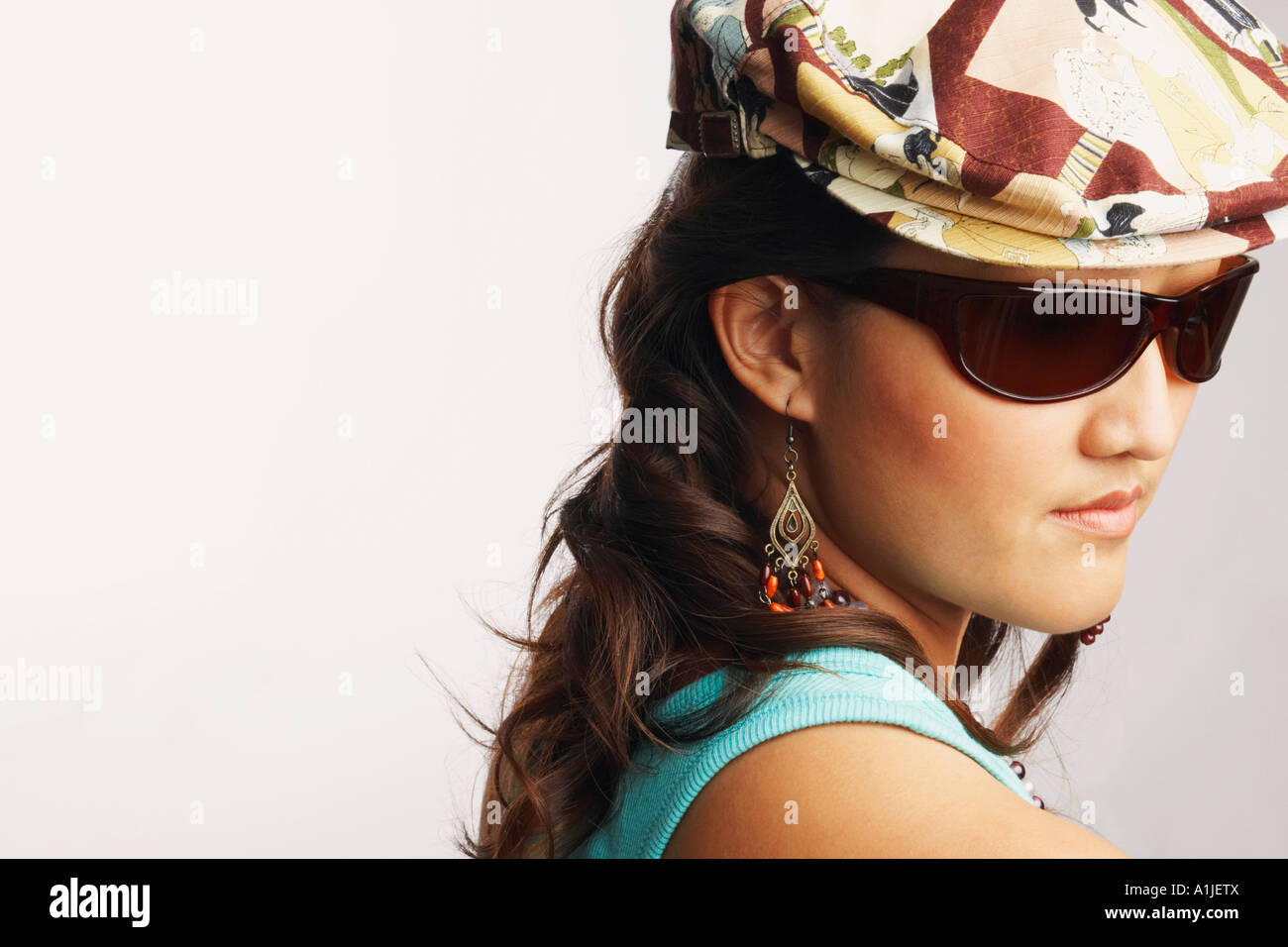 Side profile of a young woman wearing a pair of sunglasses - Stock Image