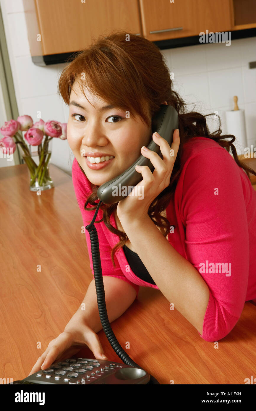 Portrait of a young woman using a telephone in the kitchen - Stock Image