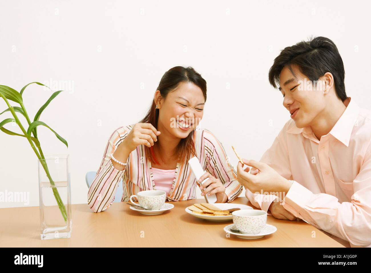 Close-up of a young couple looking at a cookie and smiling - Stock Image