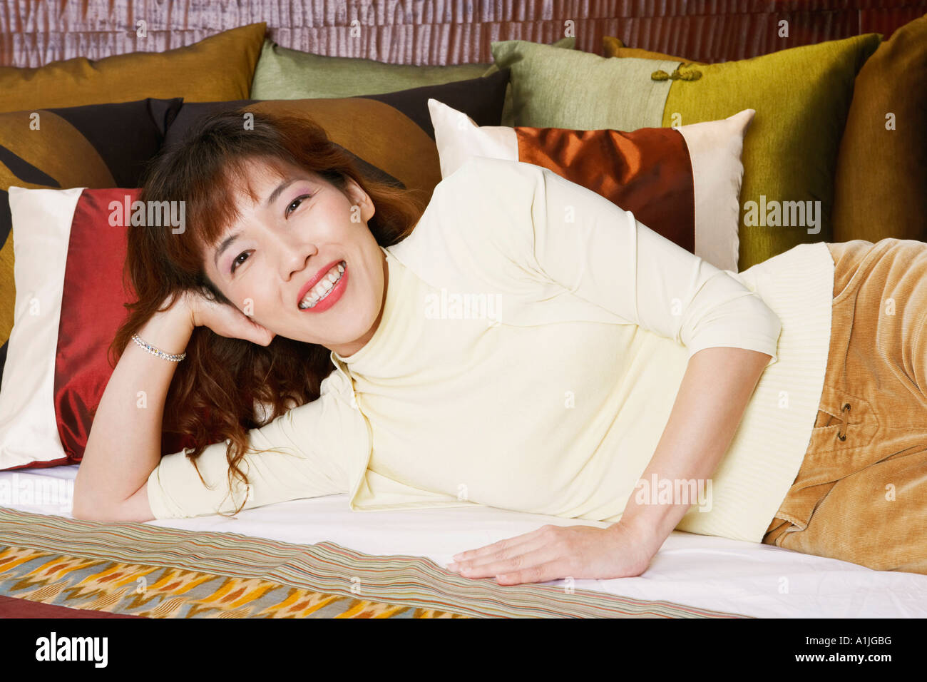 Portrait of a young woman lying on the bed and smiling - Stock Image