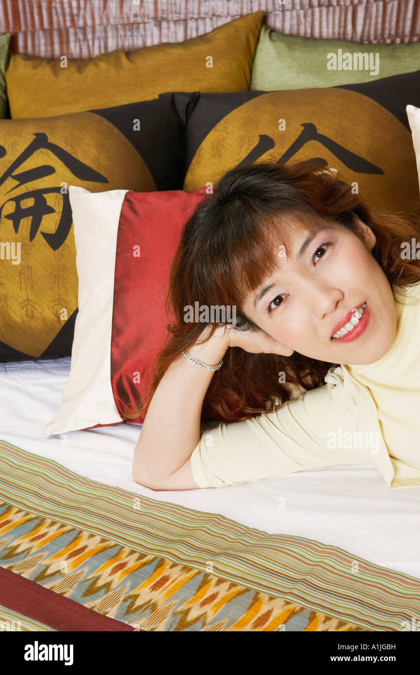 Portrait of a young woman lying on the bed - Stock Image