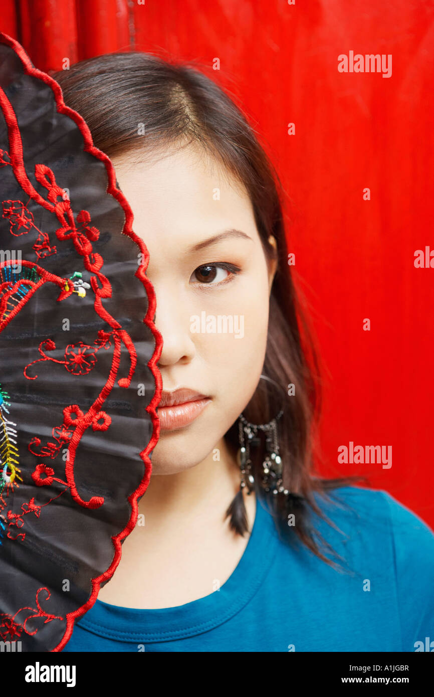 Portrait of a young woman covering her eye with a folding fan - Stock Image