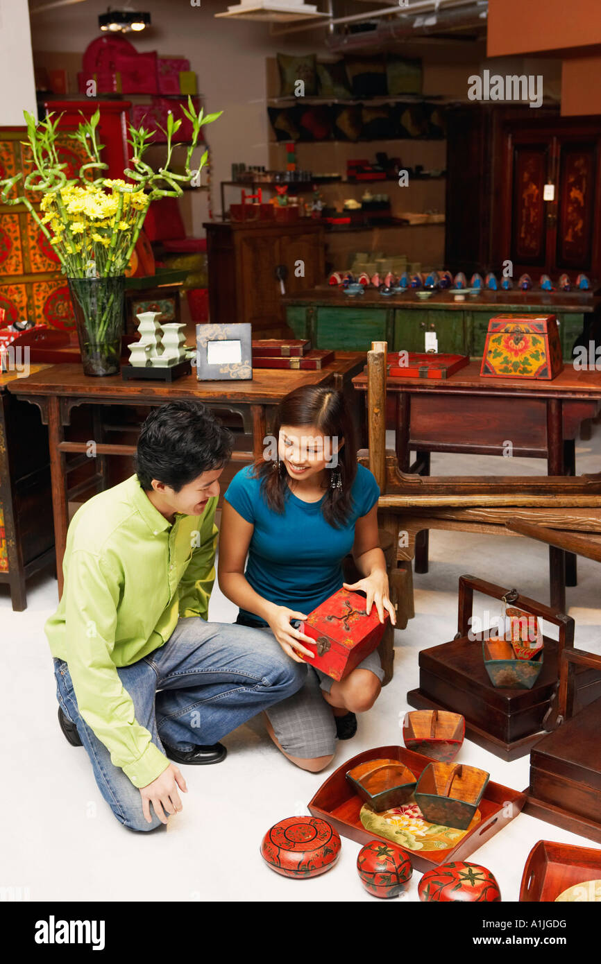 High angle view of a young man and a young couple choosing merchandise in a store - Stock Image