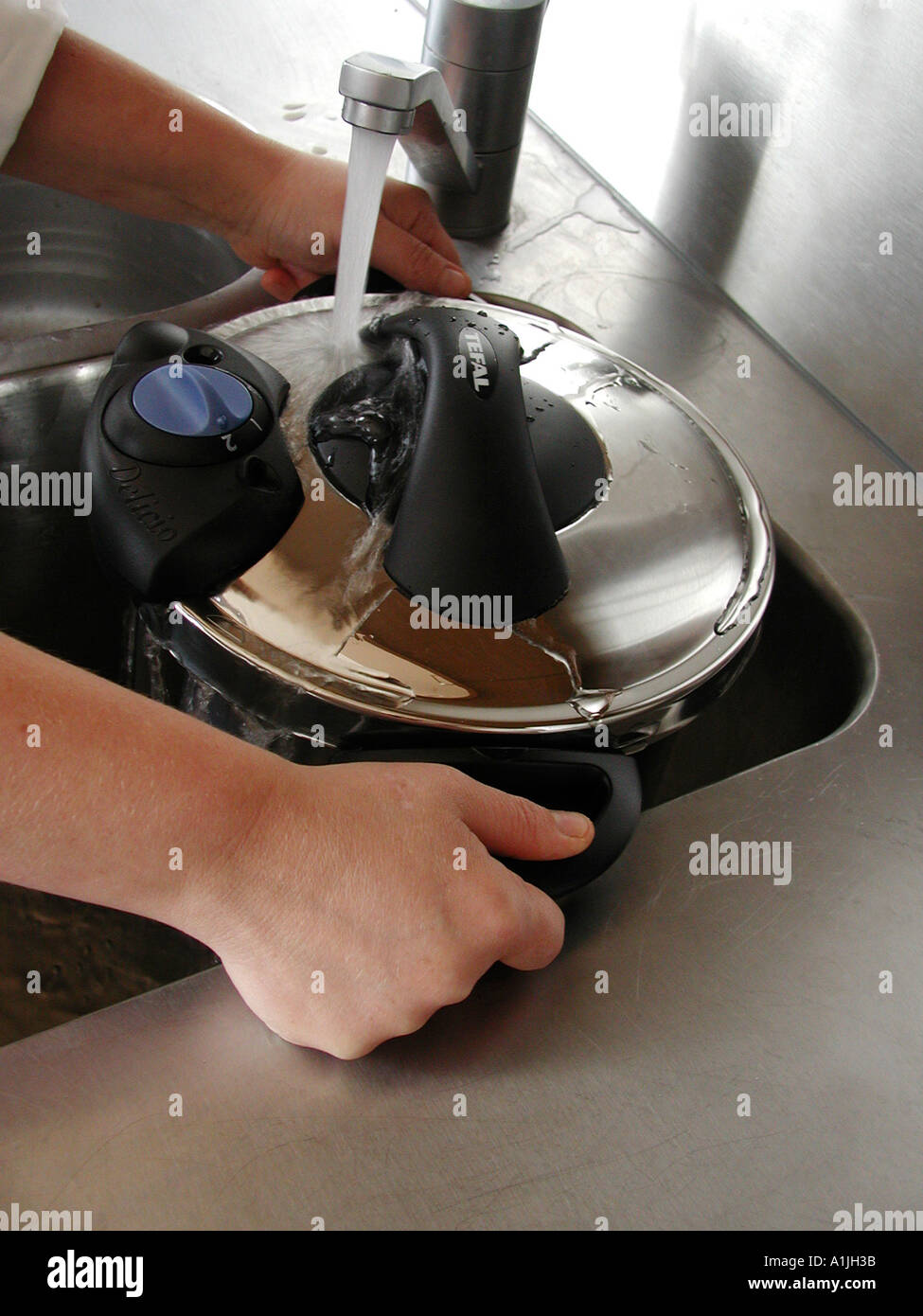 Using a pressure cooker runnung under tap to cool and reduce pressure - Stock Image