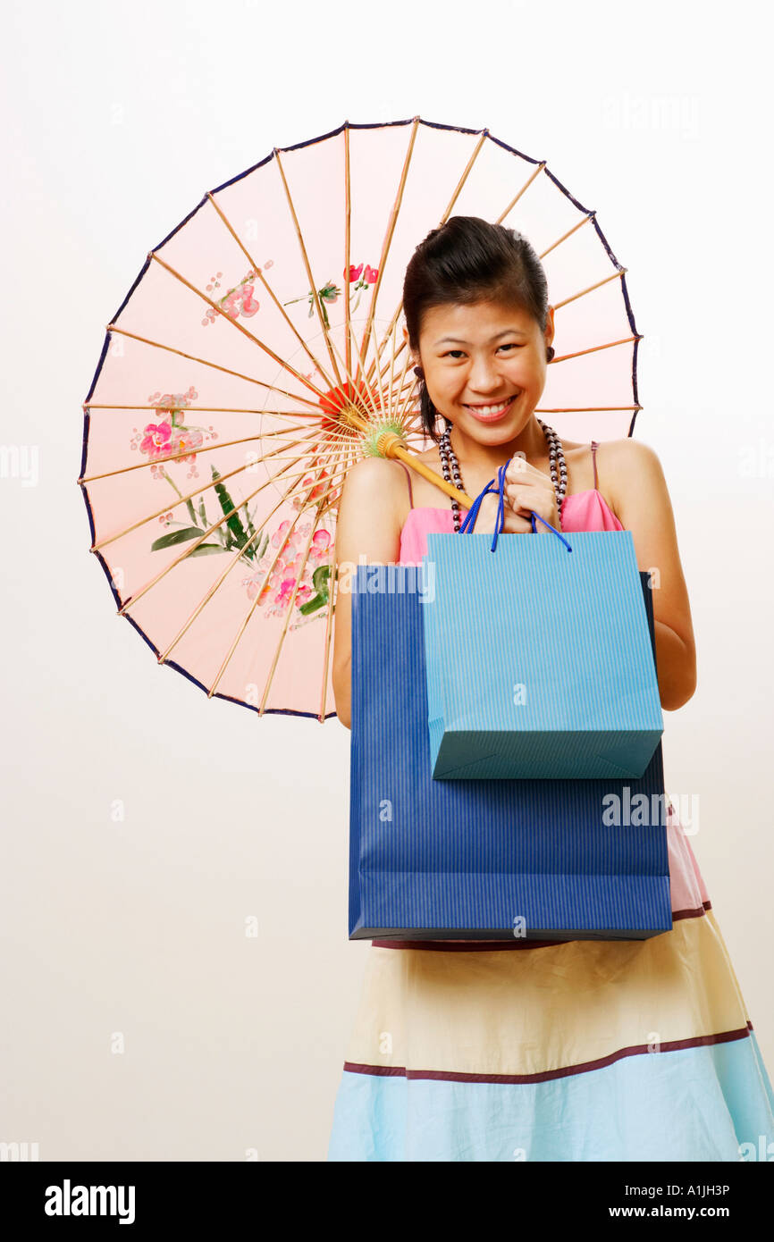 Portrait of a young woman holding a parasol and shopping bags - Stock Image