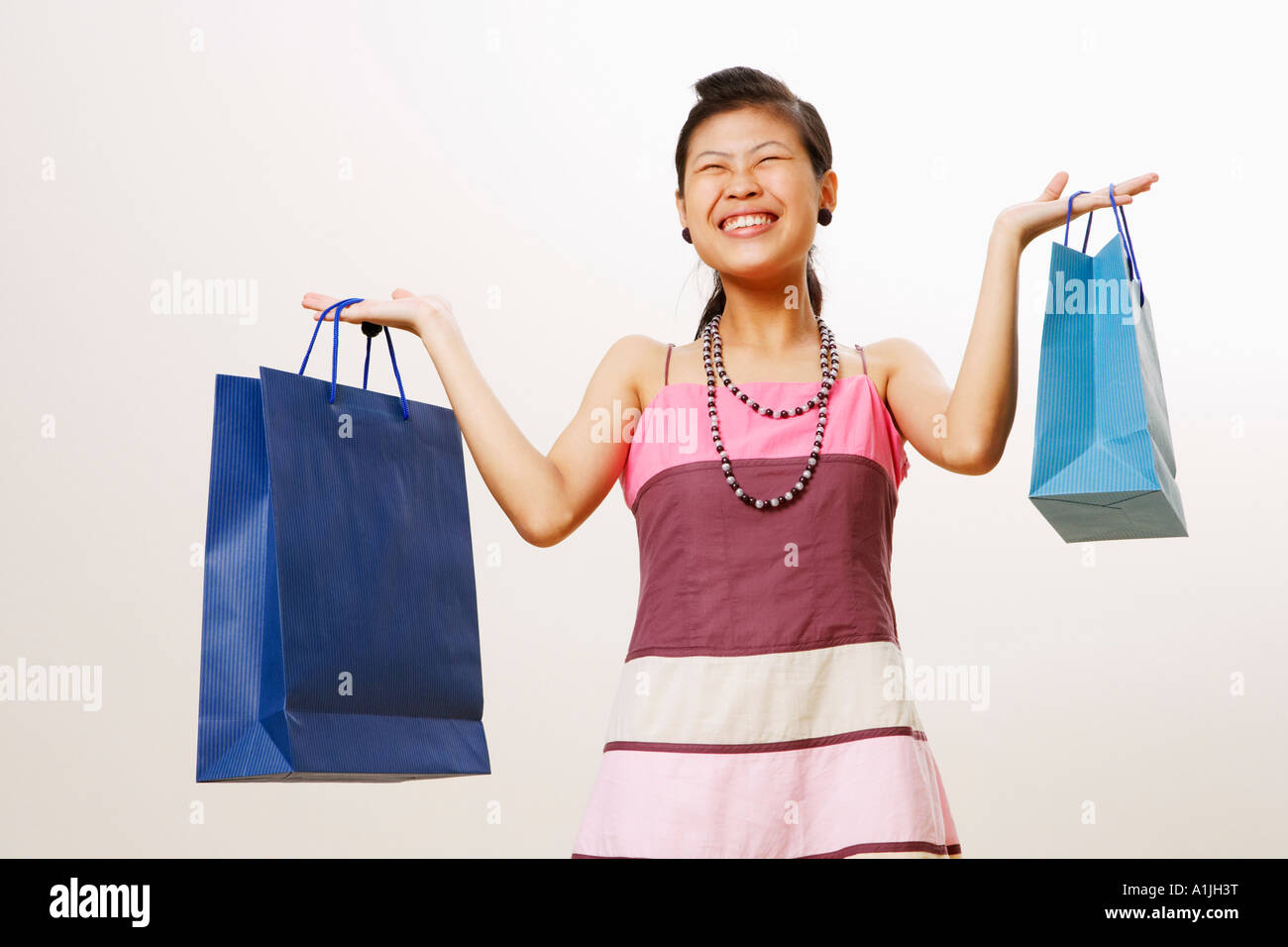 Young woman holding shopping bags with her eyes closed - Stock Image
