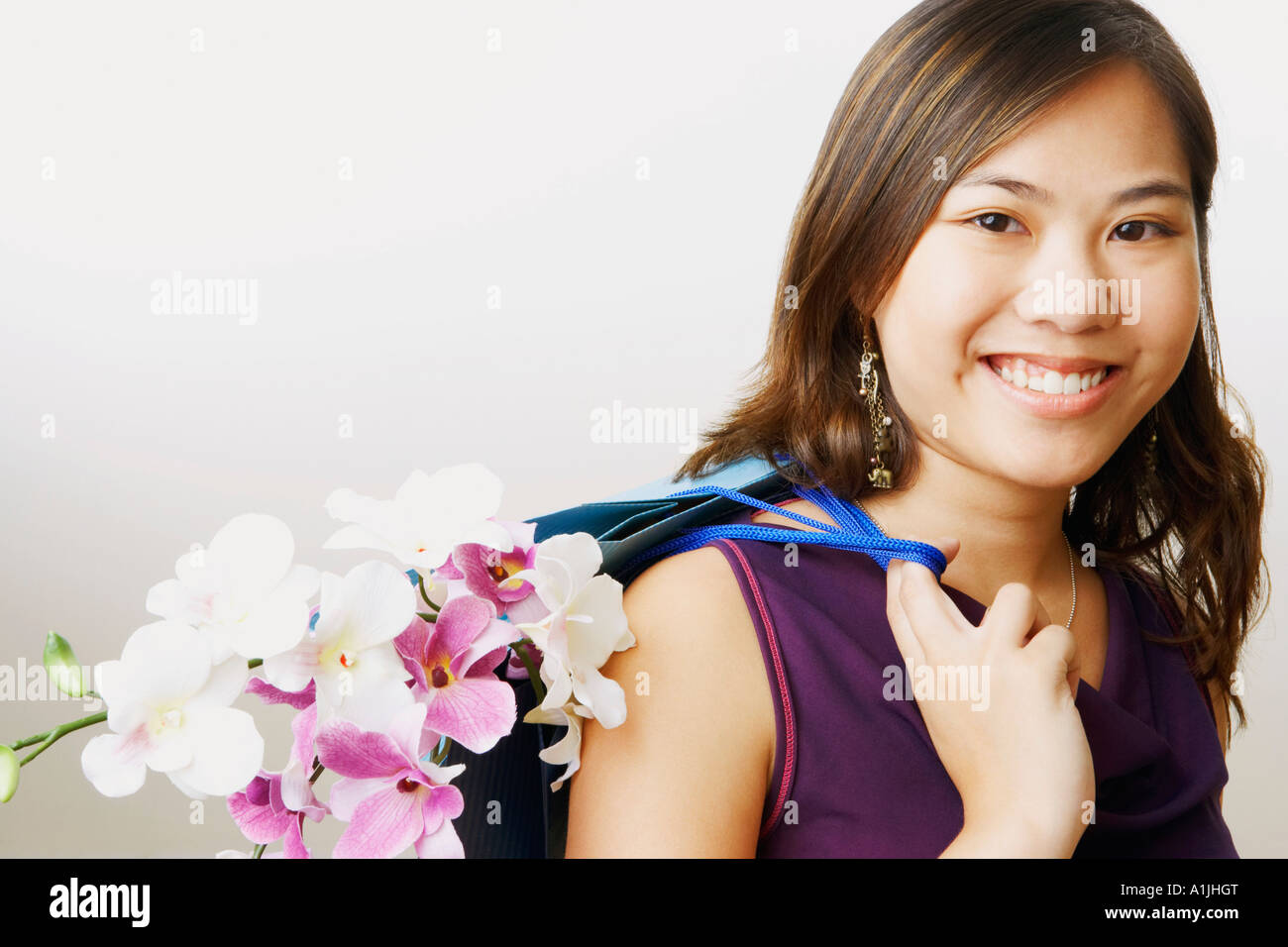 Portrait of a young woman carrying flowers in a shopping bag - Stock Image