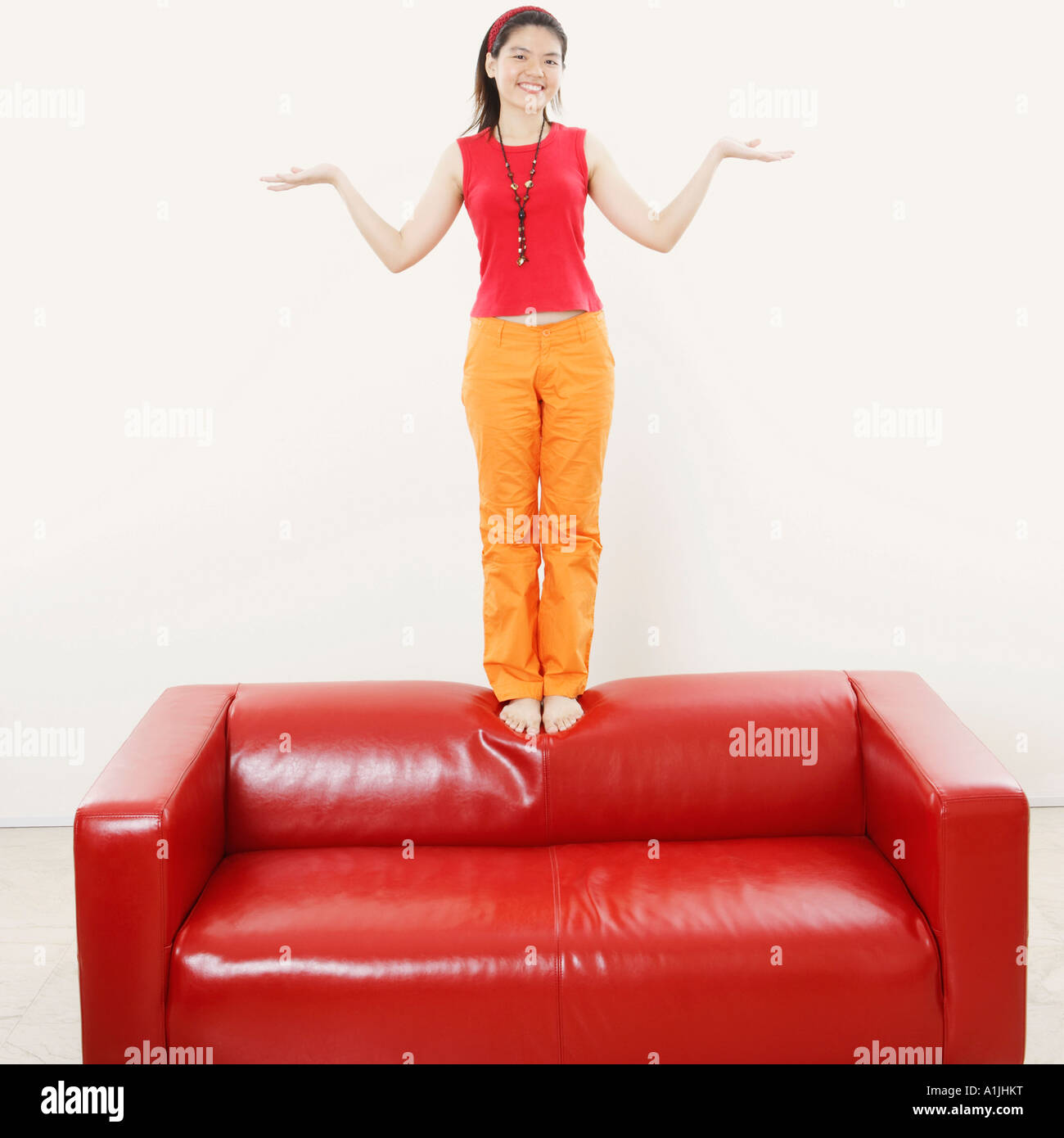 Portrait of a young woman standing on a couch and gesturing Stock Photo