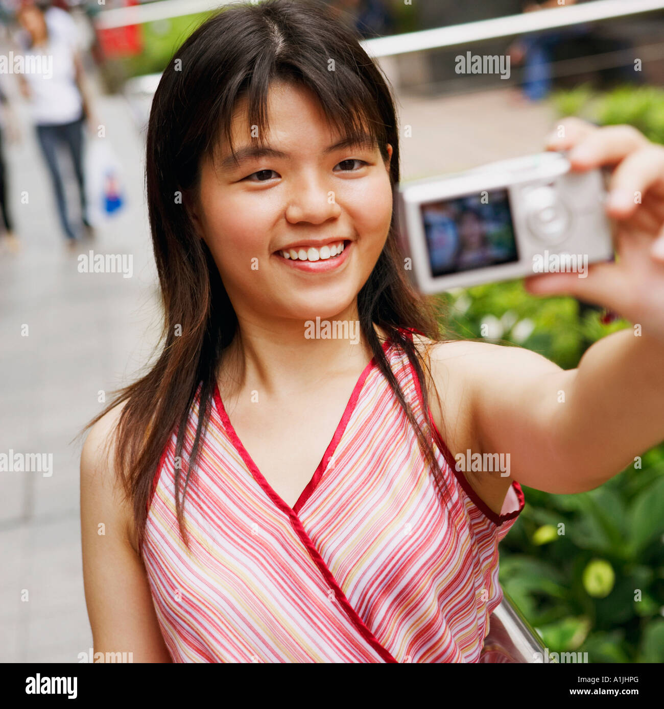 Close-up of a young woman taking a picture of herself - Stock Image