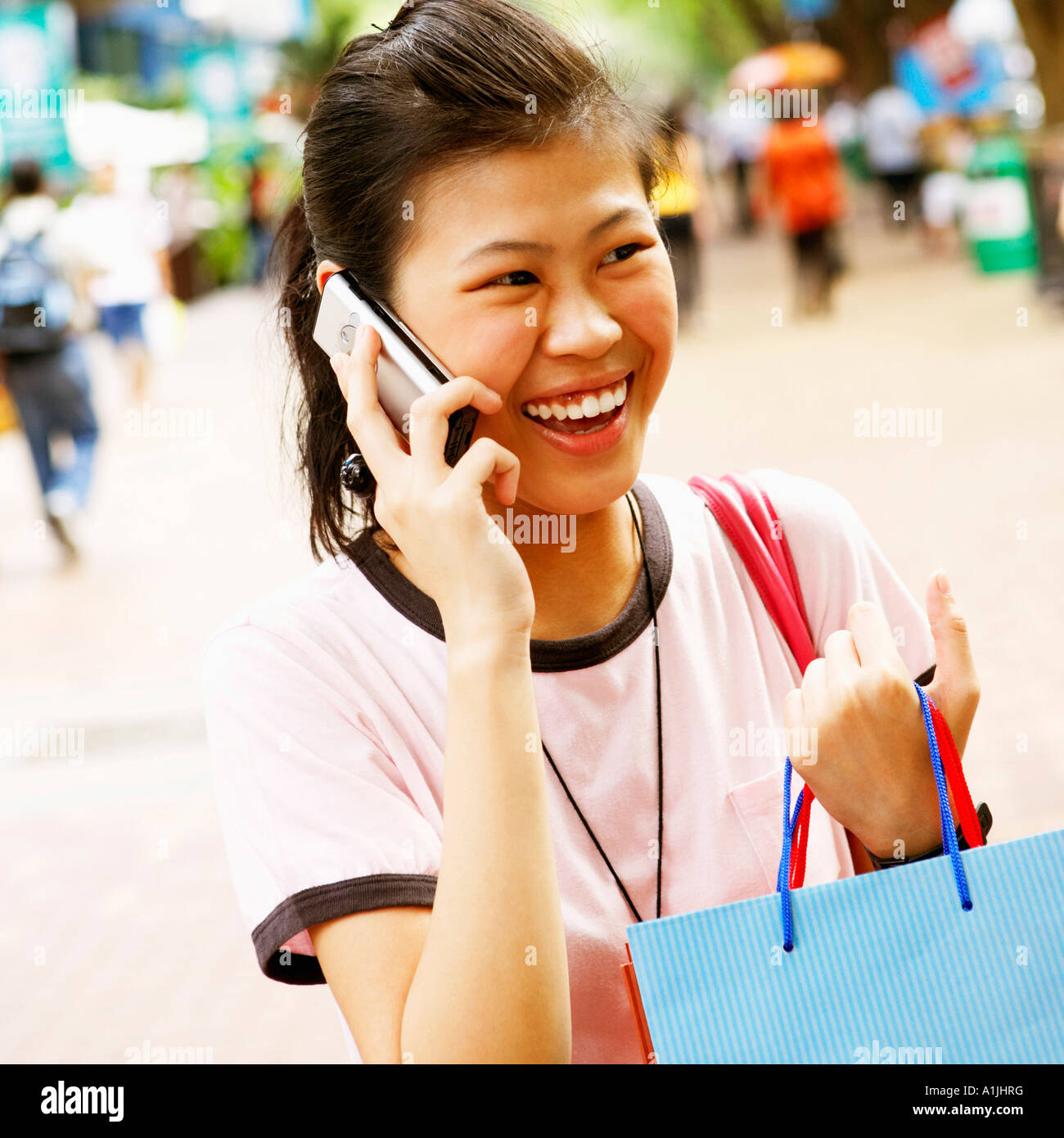 Close-up of a young woman talking on a mobile phone and carrying a shopping bag - Stock Image