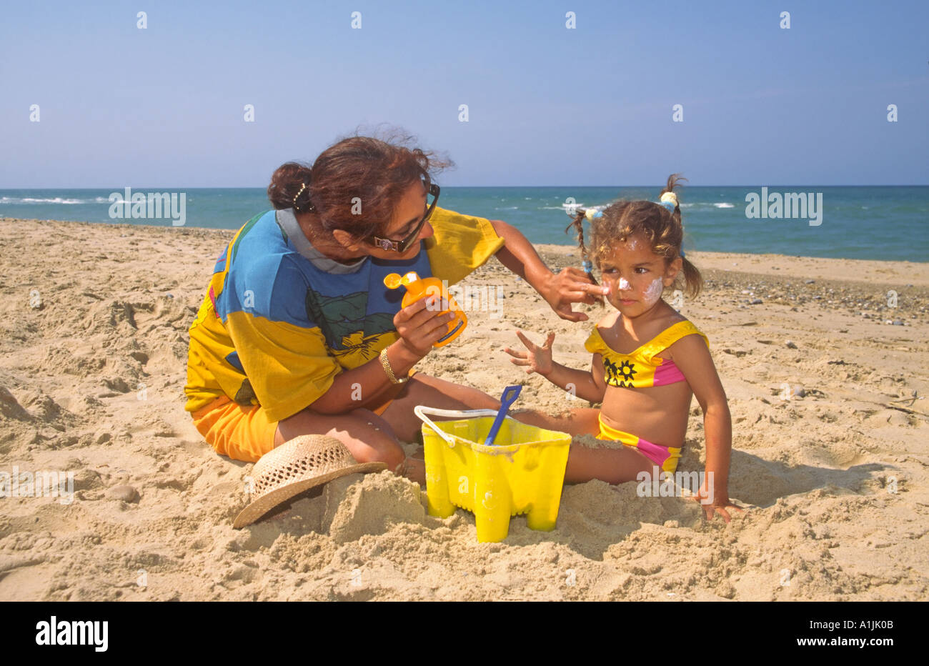 Mother Applying Suncream to Face of Child on Beach - Stock Image