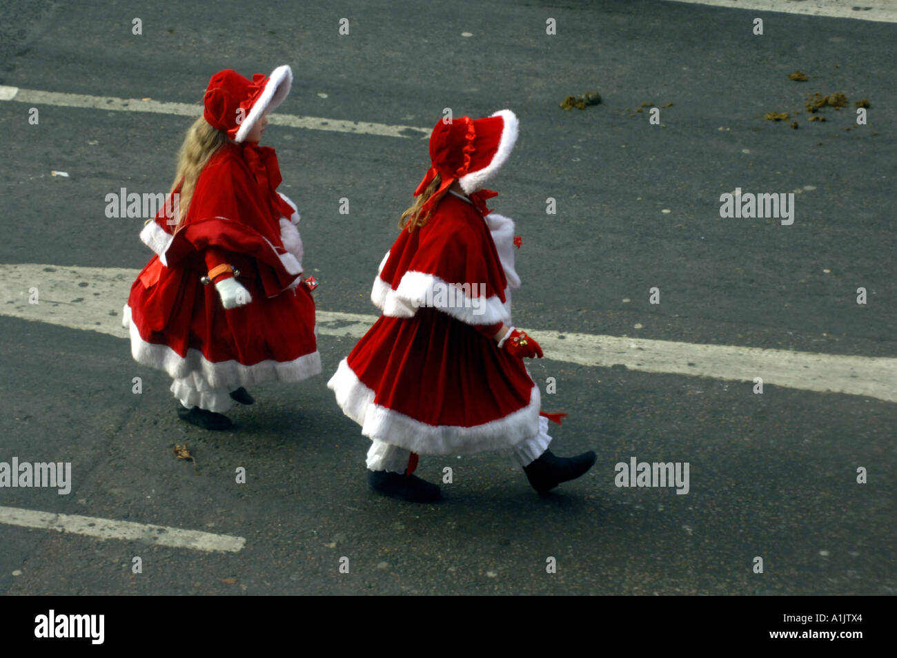 two girls youngsters red santa claus christmas outfits costumes pretty cute new years day parade mayors parade mayoral parade Lo - Stock Image