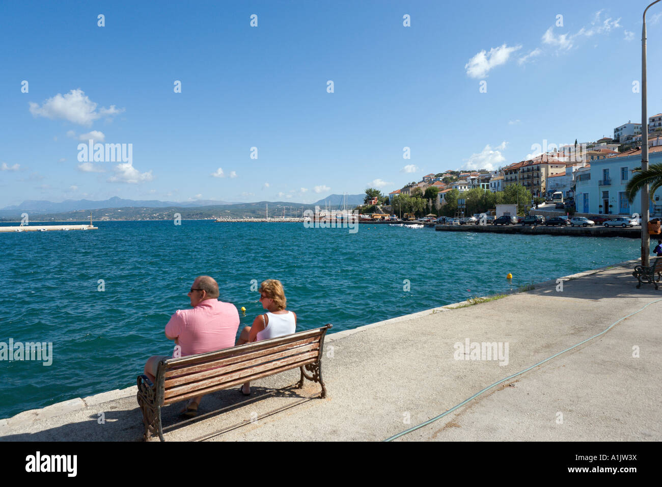 Couple sitting on the seafront in the harbour at Pylos, near Yialova, Messinia, Peloponnese, Greece - Stock Image