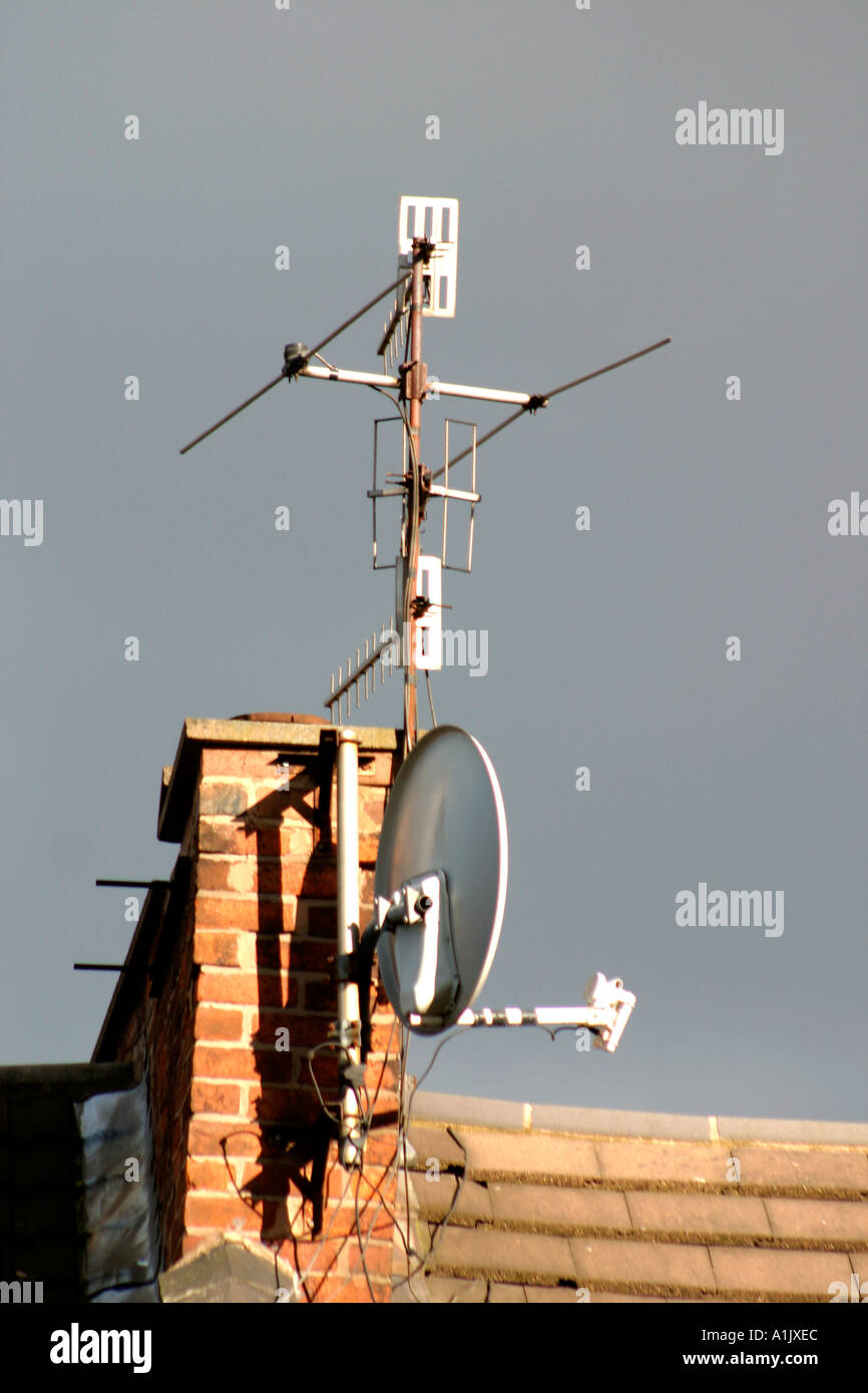 Television aerials and satellite dish on chimney stack - Stock Image
