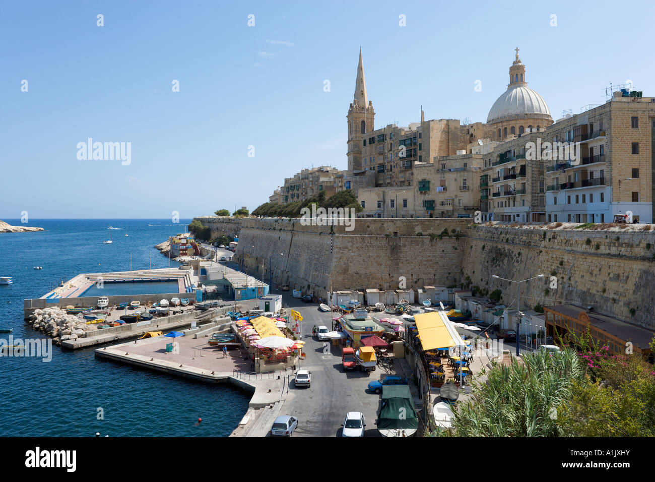 Seafront looking towards the old city with the dome of the Carmelite Church, Valletta, Malta - Stock Image