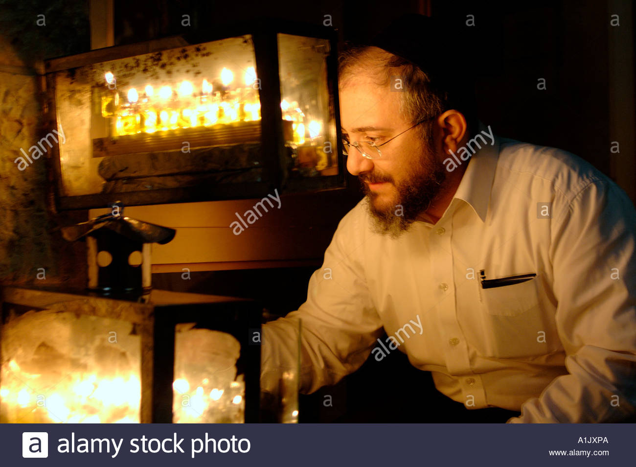Orthodox Jewish man lighting traditional Hanukkah candles on Menorah candelabrum - Stock Image