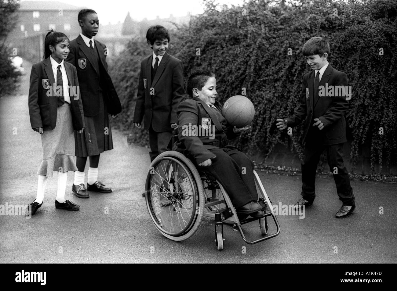 Physically disables boy in wheelchair plays ball games at break time in the school yard - Stock Image