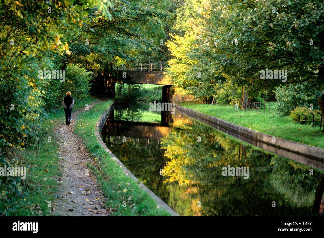 Woman walks the towpath along a narrow canal in Llangollen Wales, Great Britain - Stock Image