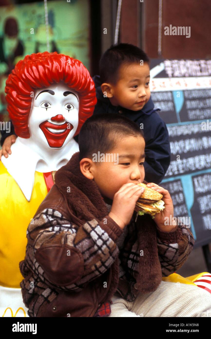 Fat chinese child eating ham burger sitting on ronald mcdonald stock fat chinese child eating ham burger sitting on ronald mcdonald mcdonalds fast food restaurant beijing china voltagebd Gallery