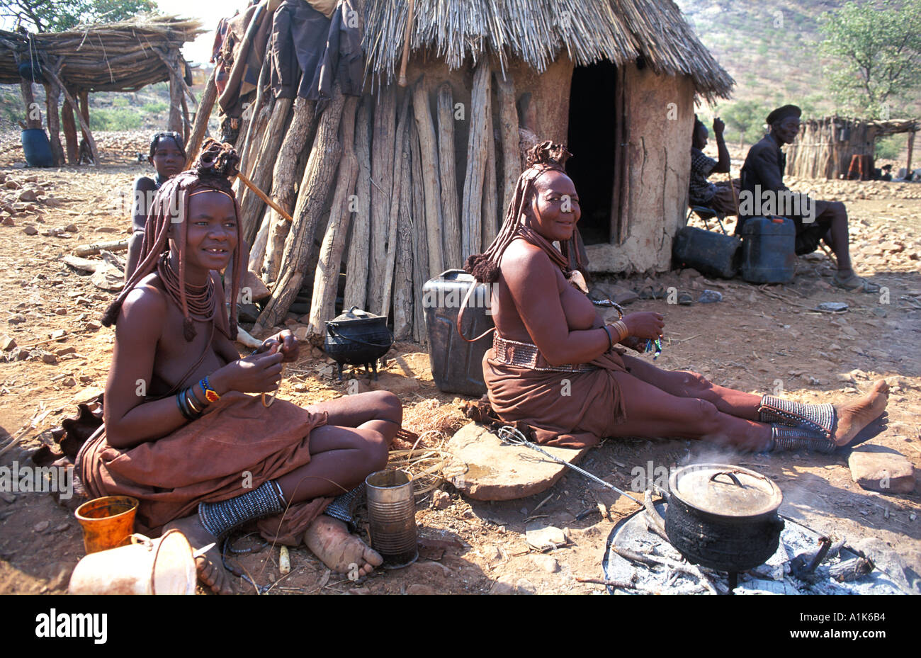 Himba women with distinctive hair decoration and adornments in their village Kaokoveld tribal areas NW of Opuwo Namibia - Stock Image