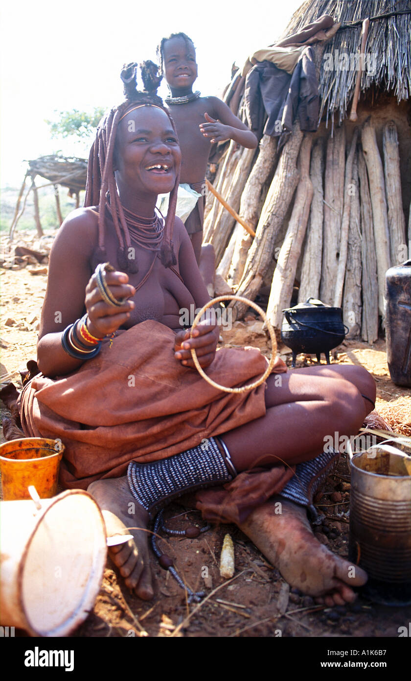 Himba woman with distinctive hair decoration and adornments in her village Kaokoveld tribal areas NW of Opuwo Namibia - Stock Image