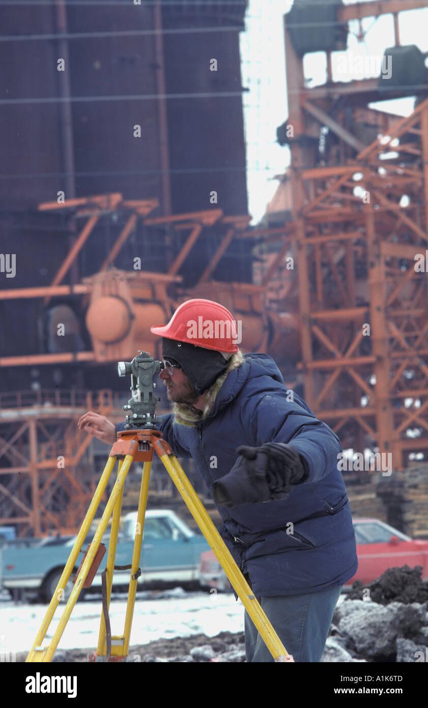 surveyor sighting trough a transit on contruction site in winter - Stock Image