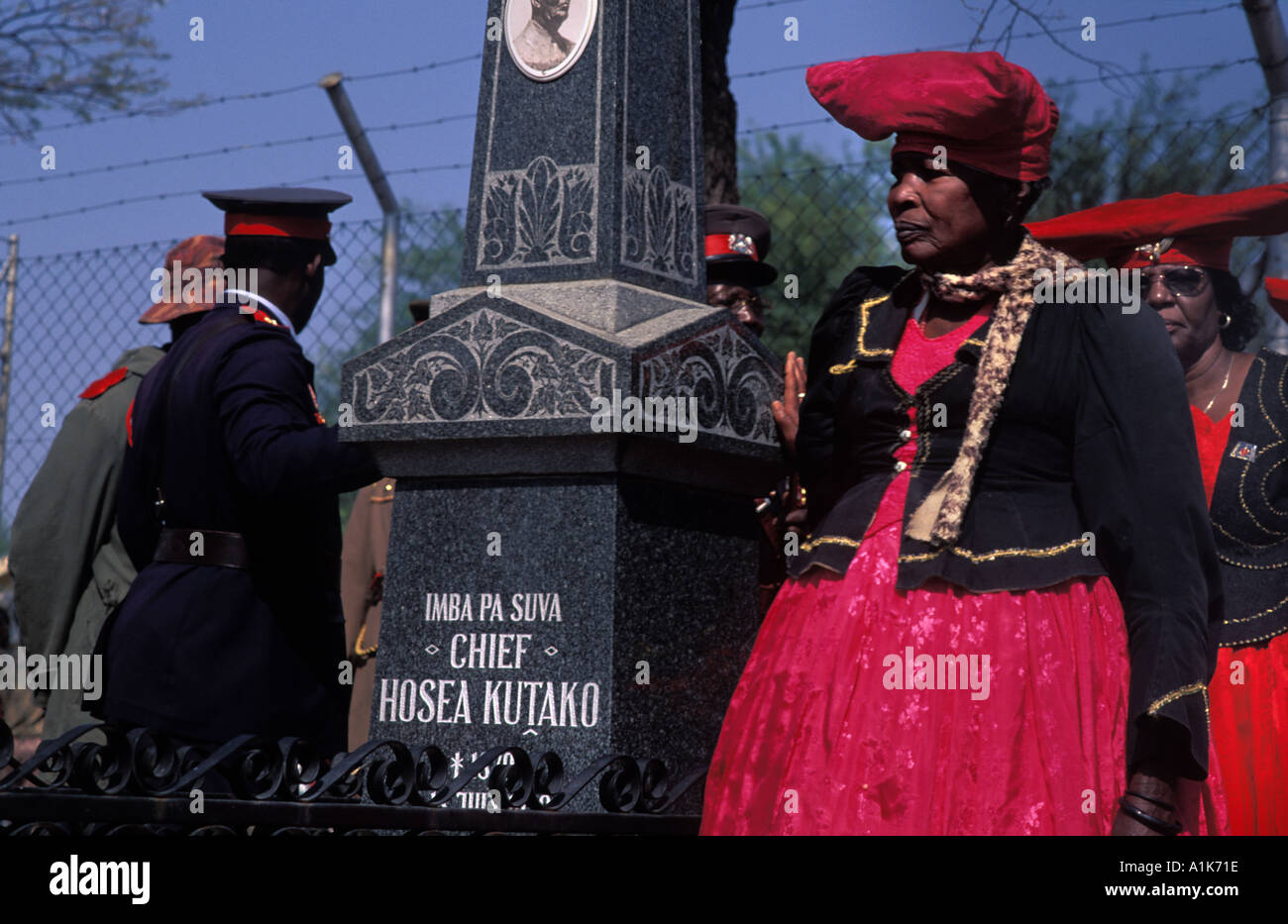 Tombstone of Chief Hosea Kutako Herero women wearing traditional dress for the MaHerero Day Parade Okahandja Namibia - Stock Image