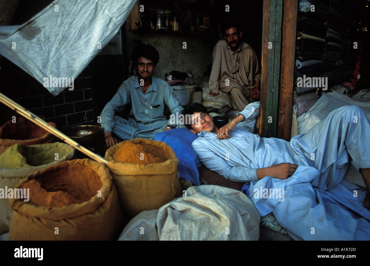 Vendors at shop selling spices relaxing Chittral NW Frontier Province Pakistan - Stock Image