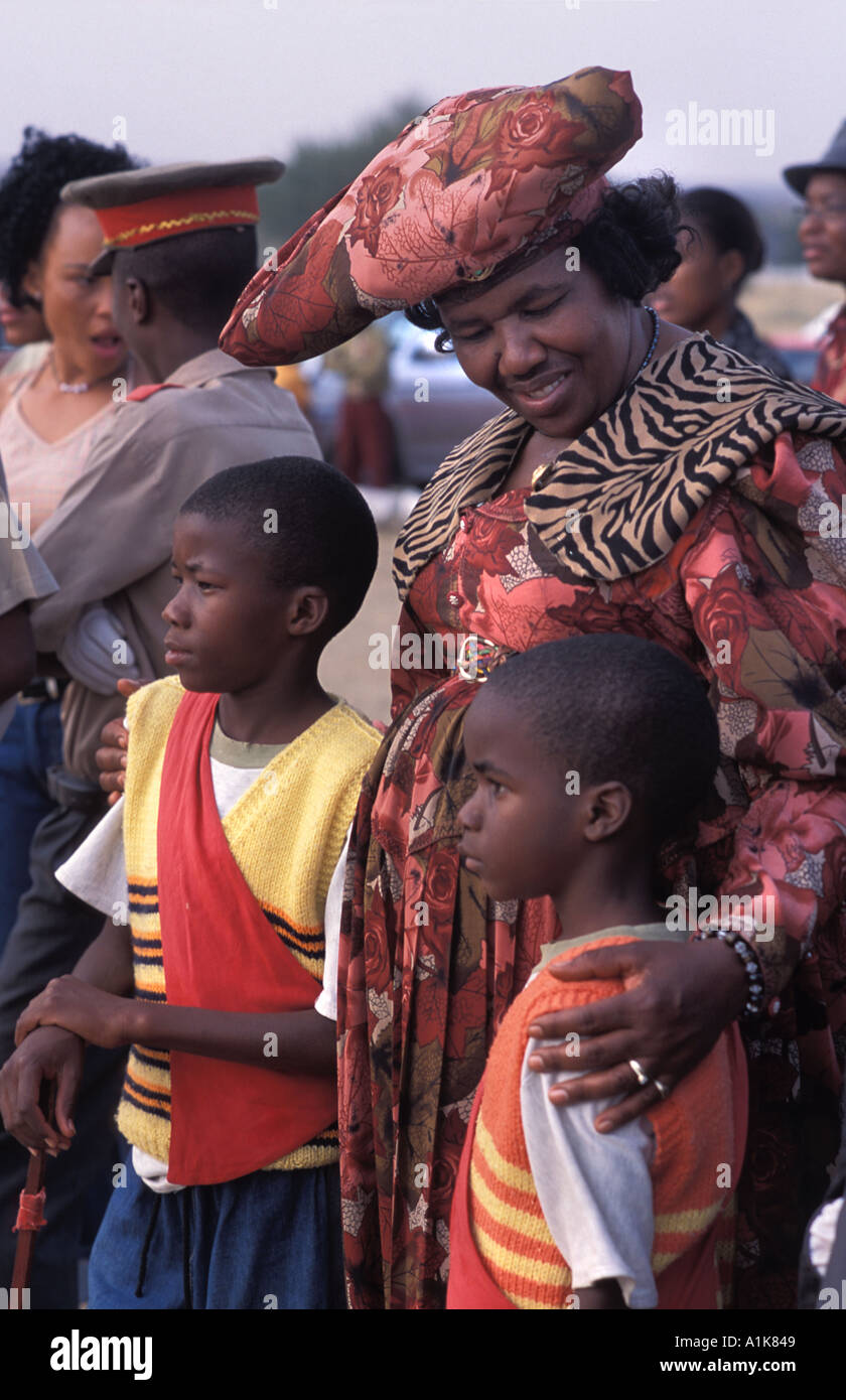 Herero woman wearing traditional dress with her children at the Ma Herero Day Parade August Okahandja Namibia - Stock Image