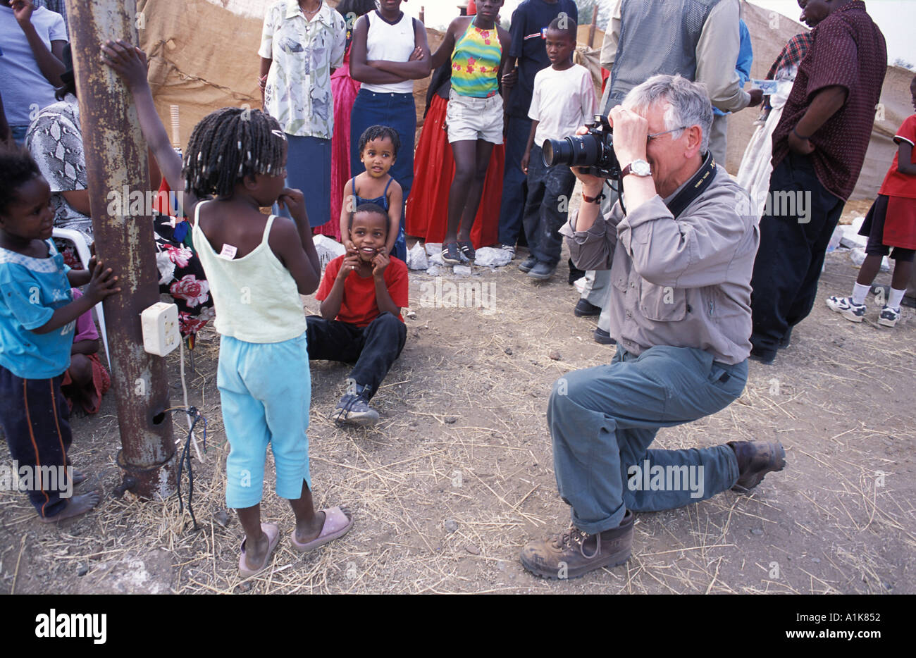 Herero girl being photographed by a professional photographer with digital camera at MaHerero Day festival Okahandja Namibia - Stock Image