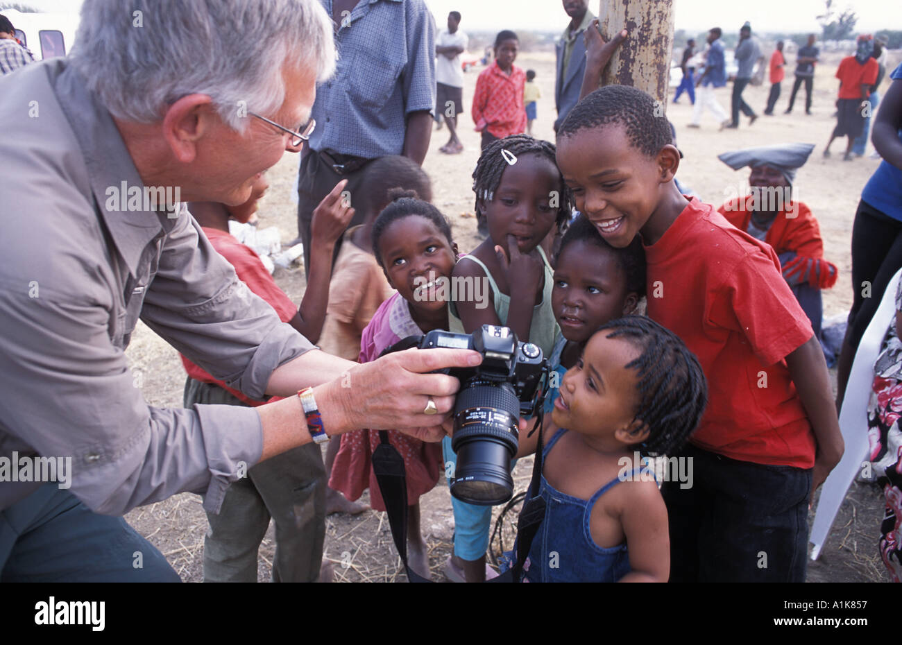 Young Herero children review their photographs on a digital camera at the MaHerero Day festival Okahandja Namibia - Stock Image
