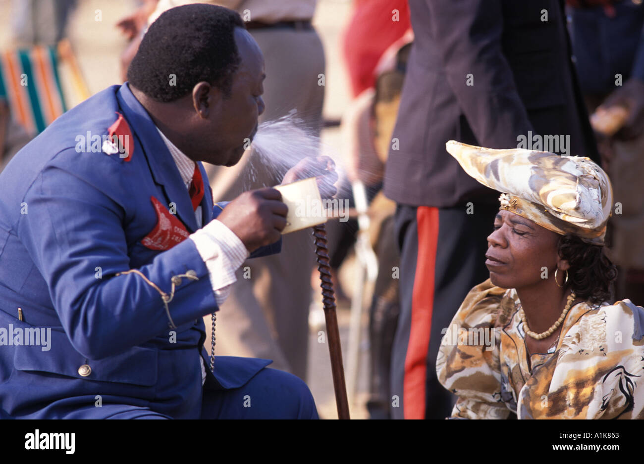 Tribal chief of paramilitary group blessing a local woman by spraying her with water alcohol Maherero day Okahandja Namibia - Stock Image