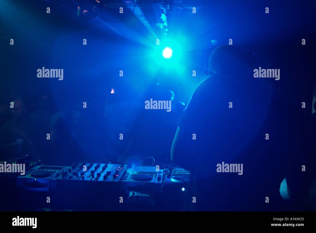 Club DJ Behind the Decks of a Crowded Nightclub. - Stock Image