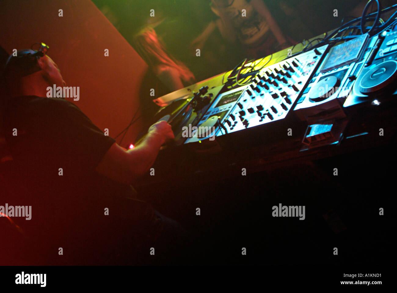 Club DJ Using a Turntable on the Decks of a Nightclub - Stock Image