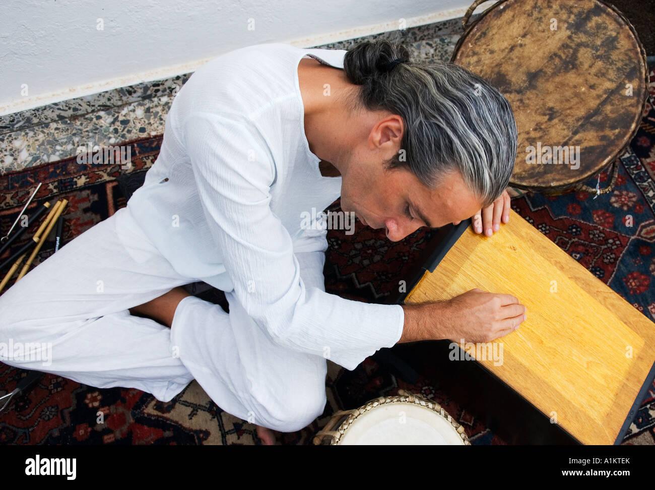 musician quietly plays a cajon - Stock Image
